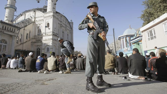 An Afghan policeman guards crowds offering the Eid al Adha's prayers outside a mosque in Kabul.