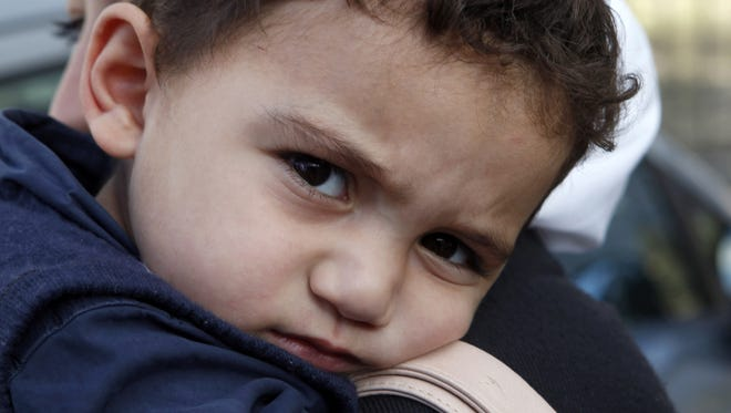 Bushr Al Tawashi looks at the photographer as he is carried by his mother Arin Al Dakkar, in Nicosia, Cyprus, Oct. 26.