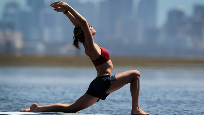 Yoga instructor Sarah Henry leads a class during a paddleboard yoga session in July 2011 at Adventure Sports Miami in Miami.