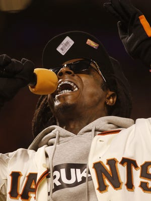 Lil Wayne performs during Sunday's National League Championship Series game.