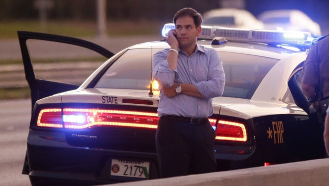 Sen. Marco Rubio, R-Fla., who is traveling with Mitt Romney, talks on the phone as he stands alongside Interstate 4 in Lakewood Crest, Fla., on Saturday.