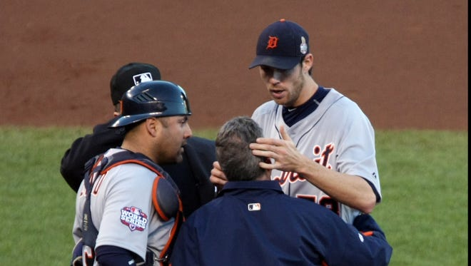 Tigers starting pitcher Doug Fister (top right) talks to trainer Kevin Rand after he was hit in the head by a line drive in Game 2.