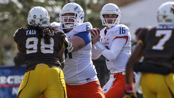 Boise State quarterback Joe Southwick (16) gets protection from teammate Joe Kellogg (61) as Wyoming defensive tackle Kurt Taufa'asau (98) pursues during the first quarter Saturday in Laramie, Wyo. Boise State beat the Cowboys 45-14.