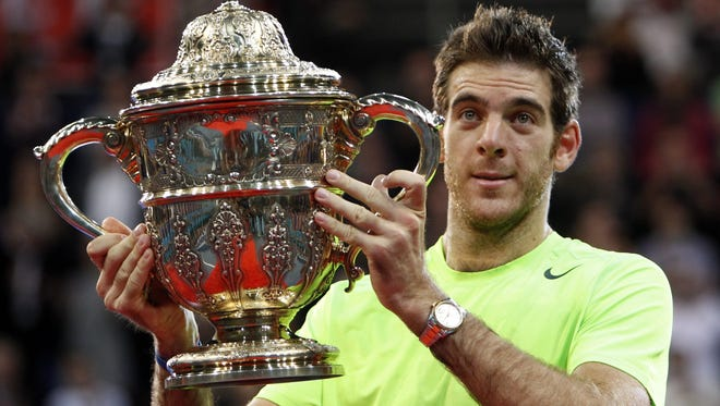 Juan Martin del Potro shows off his championship trophy after beating Roger Federer in the final of the Swiss Indoors in Basel, Switzerland.