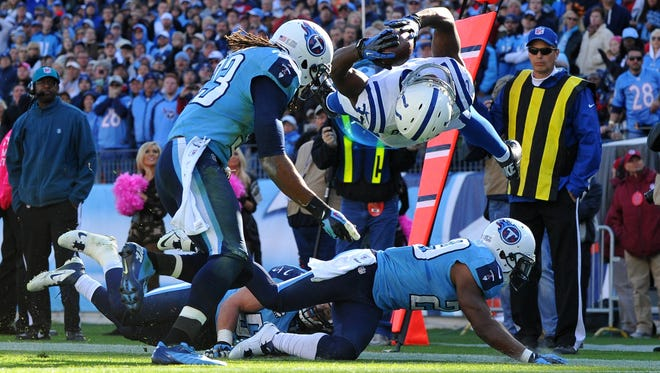 Colts running back Vick Ballard, right, soars over a pair of Titans defenders and into the end zone for the game-winning TD.