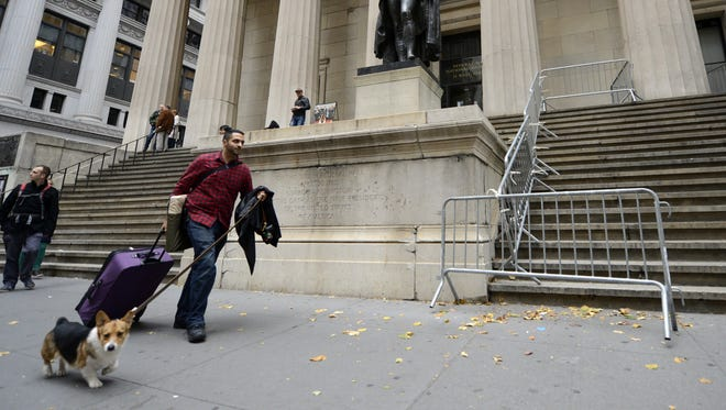 Kabir Bindra and his pet dog walk by the George Washington statue across from the New York Stock Exchange along nearly deserted Wall Street on Sunday.