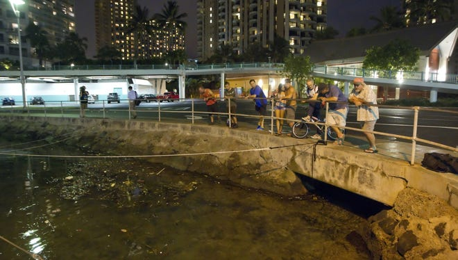 Visitors and Oahu residents watch the water level in the Ala Wai Harbor waiting for the arrival of a tsunami on Saturday.