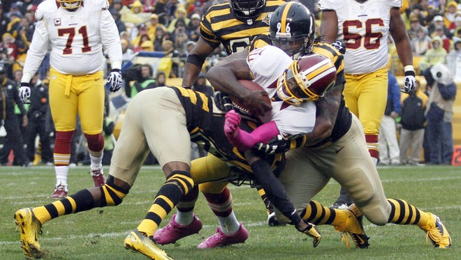 Ziggy Hood (96) and Cortez Allen (28) of the Pittsburgh Steelers tackle Robert Griffin III (10) of the Washington Redskins during Sunday's game.