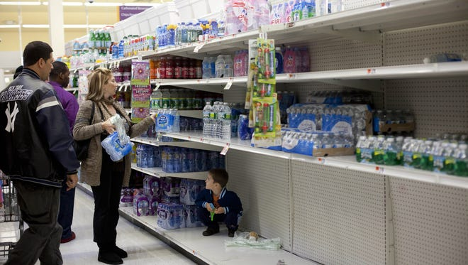 People shop for bottled water at a supermarket in Queens, N.Y., as Hurricane Sandy approaches on Sunday.