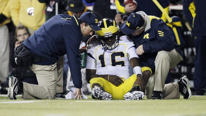 Michigan quarterback Denard Robinson injured his elbow in the first half of the Wolverines' loss.
