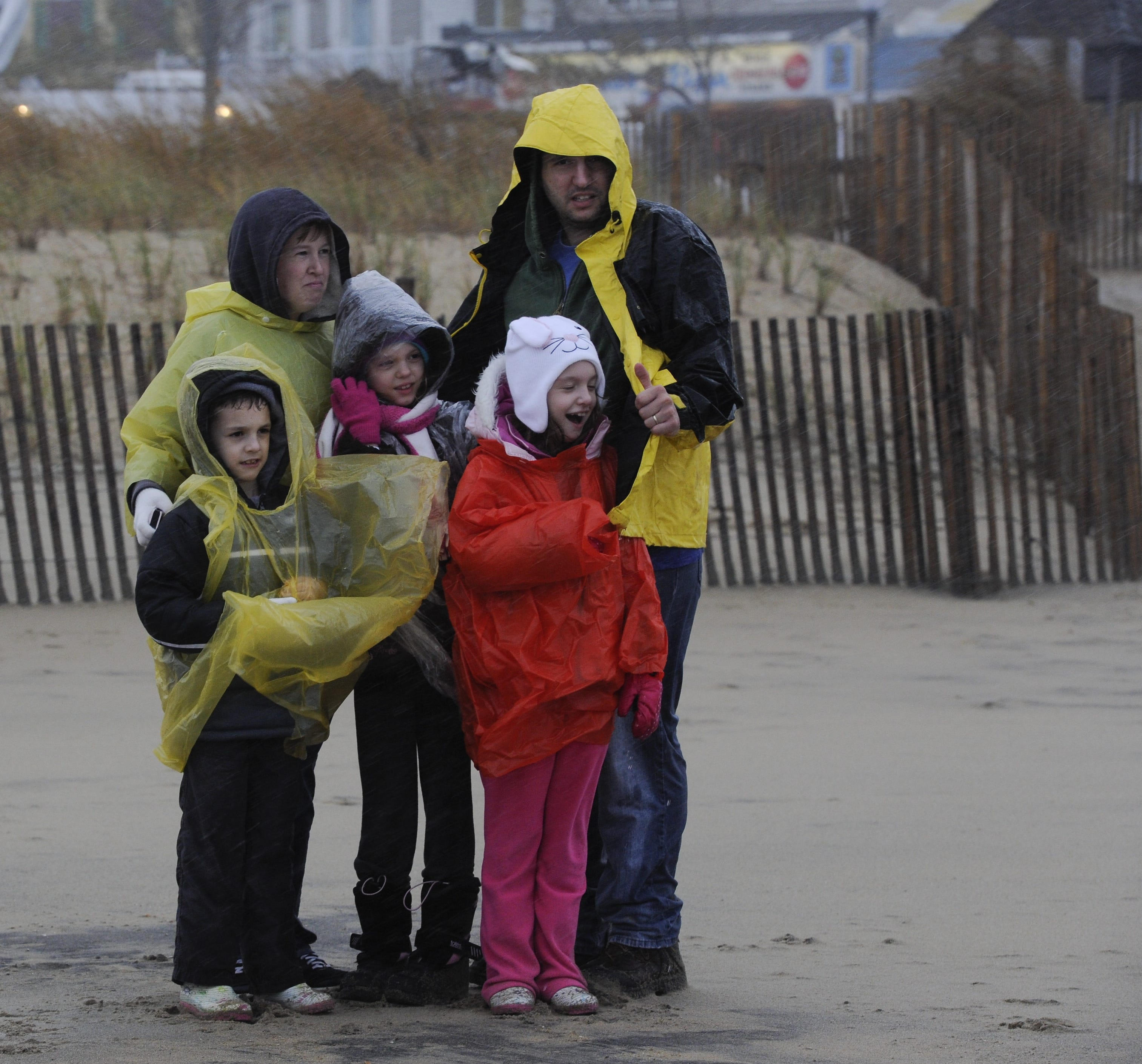 Delaware residents shield themselves as gusty winds and rain pour from the beach.