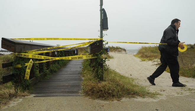 A Cape Charles police officer tapes off the town fishing pier and beach to restrict access on Sunday. Areas on the Chesapeake Bay side of the Eastern Shore of Virginia were already experiencing coastal flooding from Hurricane Sandy.