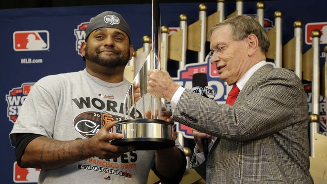 Major League Baseball commissioner Bud Selig, right, presents the World Series MVP trophy to Giants third baseman Pablo Sandoval following the Giants' sweep of the Detroit Tigers.