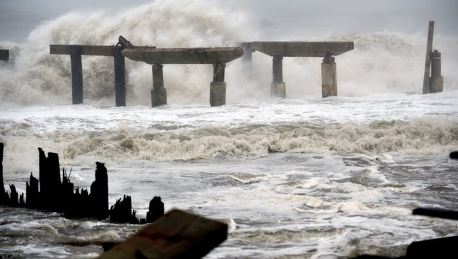 Waves crash against a previously damaged pier before landfall of Hurricane Sandy on Monday in Atlantic City, N.J.