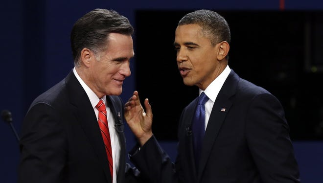 Mitt Romney and President Obama talk after the first presidential debate at the University of Denver.