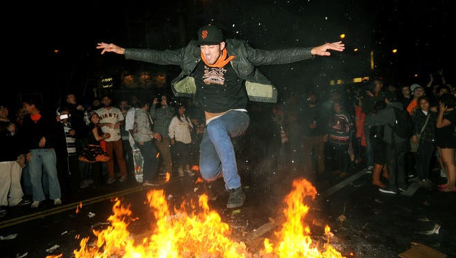 A San Francisco Giants fan jumps over a bonfire in San Francisco's Mission district Sunday, Oct. 28.