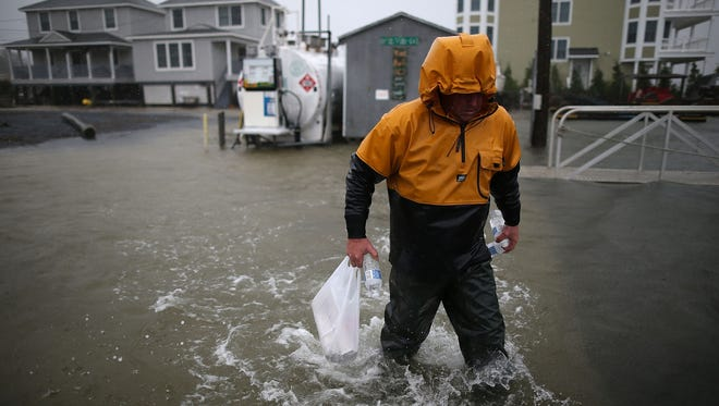 A man walks through flood waters caused by Hurricane Sandy in Cape May, New Jersey.