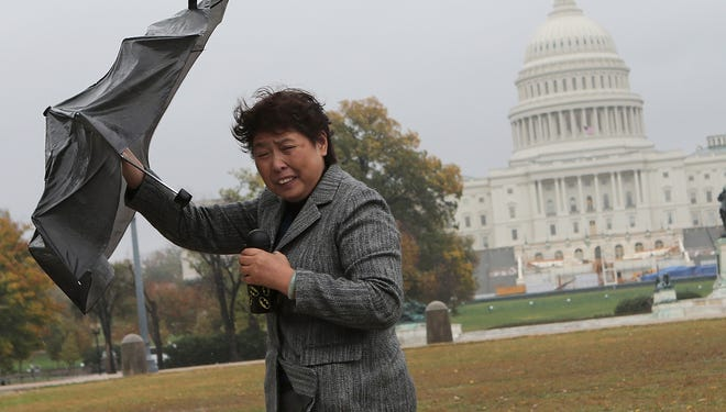 A tourist struggles against gusting winds as the leading edge of Hurricane Sandy moves across the nation's capital on Monday in Washington, D.C.