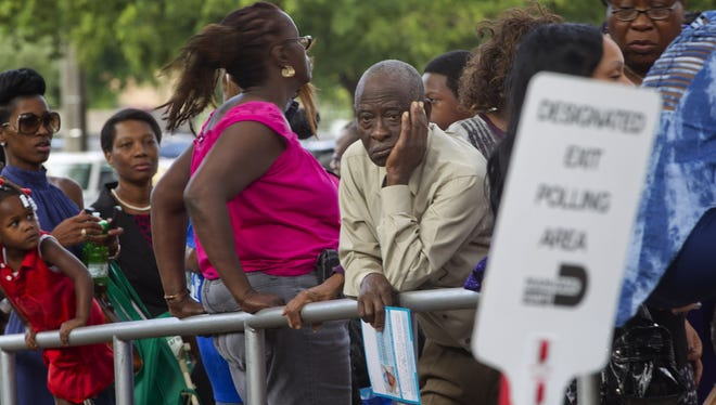 People wait to in line Sunday to vote early in Miami.