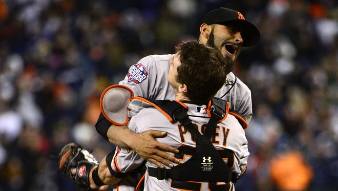 Giants pitcher Sergio Romo and catcher Buster Posey celebrate defeating the Tigers in four games.