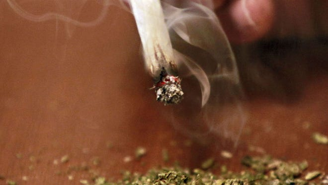 A joint over some ground marijuana.
