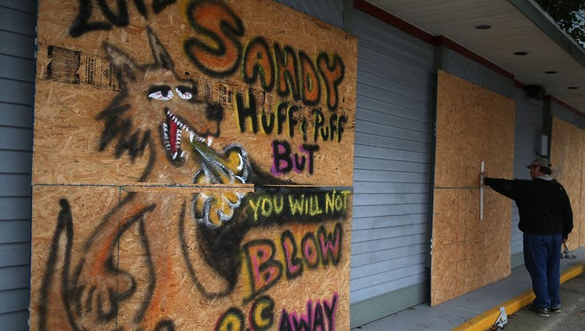 Ed Wicks secures plywood over the windows of his business to protect from the high winds of approaching Hurricane Sandy, on Oct. 28, 2012, in Ocean City, N.J.