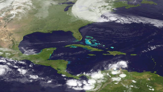 A satellite image released by the National Oceanic and Athmospheric Administration shows hurricane Sandy (top) moving north on the Northeast coast of the United States.