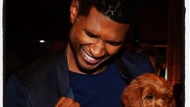 Usher celebrates his winning charity bid that netted him a new puppy.