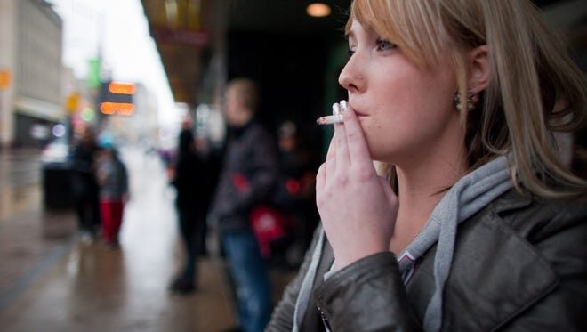 A woman smokes a cigarette in London, Ontario. A new study shows that women who quit smoking by age 40 can add a decade to their lives.