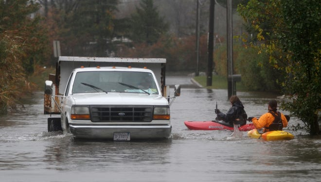 South River, NJ - Kayakers paddle past a utility truck along Elizabeth Street in South River, N.J., on Oct. 29 in the hours before the landfall of Hurricane Sandy.