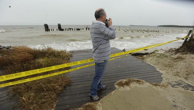 Greg Kohler takes photographs of storm damage from Hurricane Sandy at Cape Charles, Va.