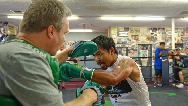 Manny Pacquiao works the mitts with trainer Freddie Roach on his first day of training camp Monday at roach's Wild Card Gym for his upcoming fight against Juan Manuel Marquez.