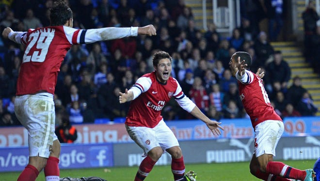 Theo Walcott, right, celebrates scoring Arsenal's sixth goal with teammates Marouane Chamakh, left, and Olivier Giroud.