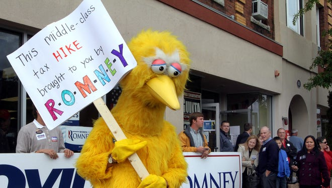 A person dressed up as Big Bird holds a sign against Republican presidential candidate Mitt Romney on Oct. 8 outside the Romney headquarters in Derry, N.H.