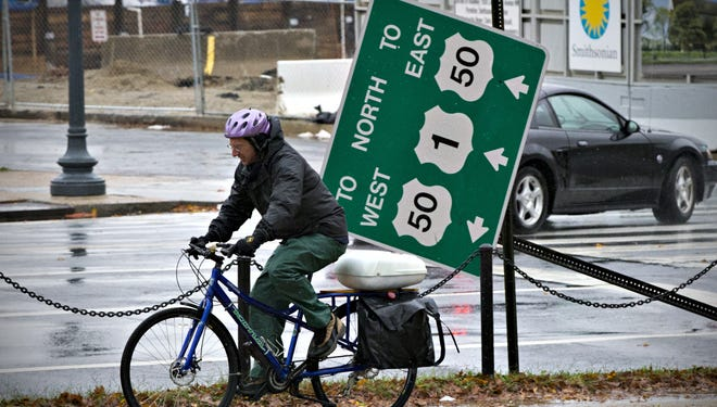 A cyclist rides past a wind-blown traffic sign in downtown Washington on the morning after Hurricane Sandy passed through the nation's capital.