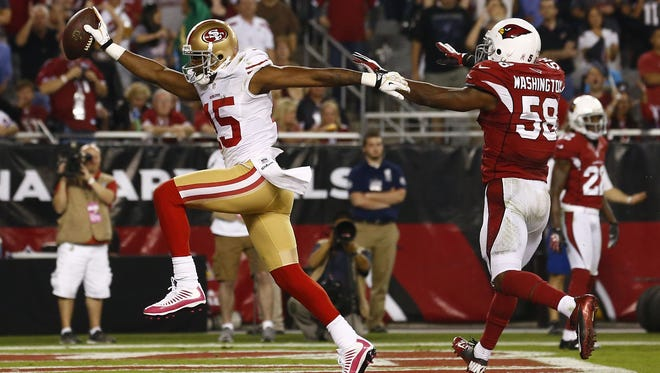 49ers wide receiver Michael Crabtree (cq) high-steps into the end zone for a touchdown past Cardinals linebacker Daryl Washington on Monday night at University of Phoenix Stadium.