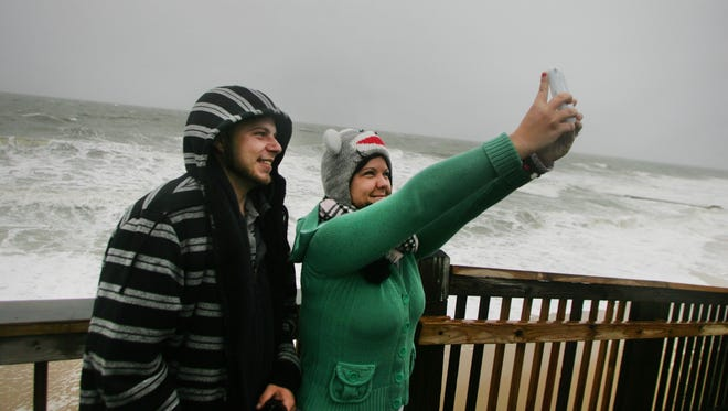 Lisa and Michael Chamberlain, a newlywed couple on their honeymoon, take a cell phone picture of themselves with the pounding surf from Hurricane Sandy in the background in Virginia Beach, Va.