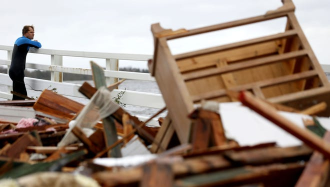 Currie Wagner looks at the wreckage of his grandmother Betty Wagner's house, which was destroyed and wound up resting on top of the Mantoloking Bridge the morning after hybrid storm Sandy rolled through, Tuesday.