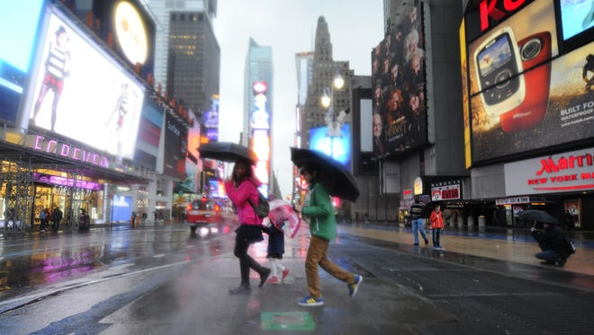 Tourists walk through Time Square in New York on Monday morning during the storm.
