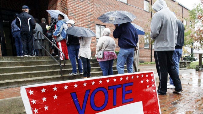 Voters wait in line despite rains from Hurricane Sandy to vote on the last early voting Sunday before election day in New Bern, N.C.