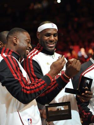Heat teammates Dwyane Wade and LeBron James admire their new NBA championship rings.