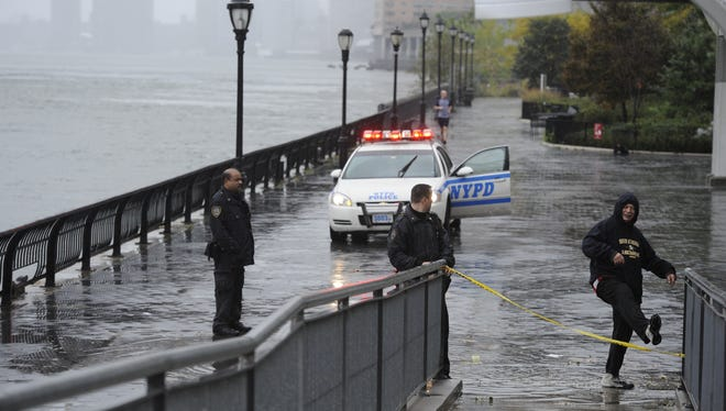 New York police clear the walkways along the East River as the water rises Monday.