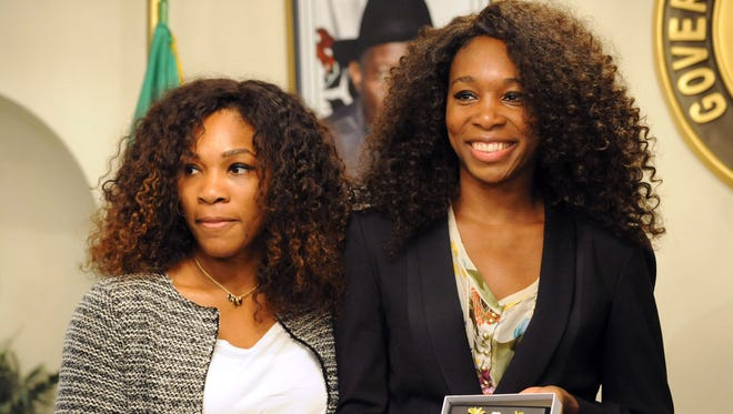 Serena and Venus Williams hold the emblems of the state government they received during a visit at the government house in Lagos, Nigeria, on Wednesday. They are part of a two-nation tour that will see them play exhibition matches to promote women's rights.
