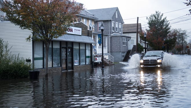 A truck drives down a flooded street after water levels lowered in Little Ferry, New Jersey.