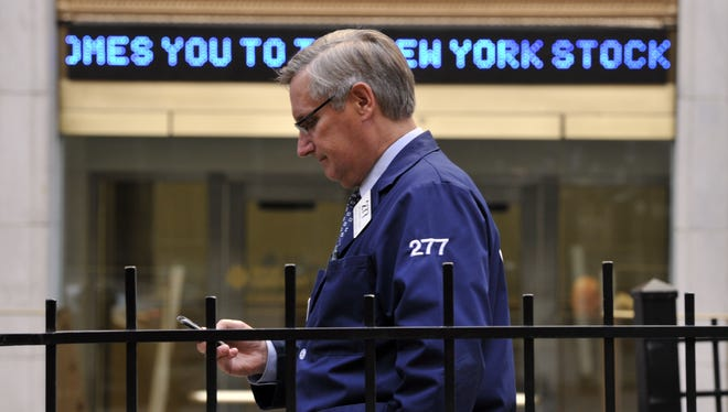 A trader stands outside the New York Stock Exchange as people return to work on Wall Street October 31, 2012.