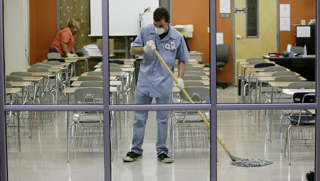 Workers disinfect a classroom at Byron P. Steele High School in Cibolo, Texas, Monday, April 27, 2009. The school was closed due to a flu outbreak.  A new study suggests such closures help control the spread of flu. (AP Photo/Eric Gay)