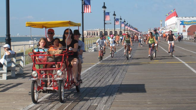 Bicyclists ride the boardwalk in Ocean City, N.J., in August, as the last few days of the summer vacation season tick away.