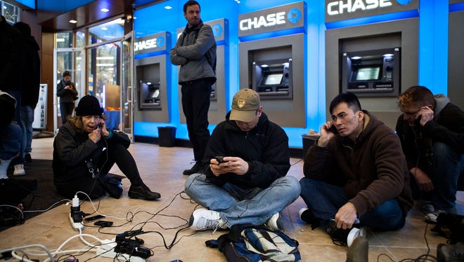 People crowd into a Chase Bank ATM kiosk to charge phones and laptops at 40th Street and 3rd Avenue, one block north of where power has gone out, on October 31, 2012, in New York City.
