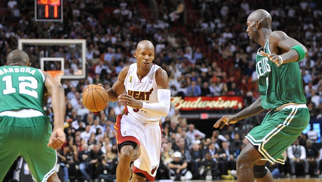 Heat guard Ray Allen drives past Celtics center Kevin Garnett during Miami's 120-107 season-opening win Tuesday