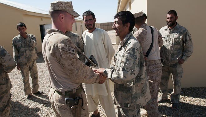 Marine Maj. Max Hopkins, commanding officer of Battalion Advisor Team 1, meets with Afghan Border Police at their headquarters last month  near Taghaz.